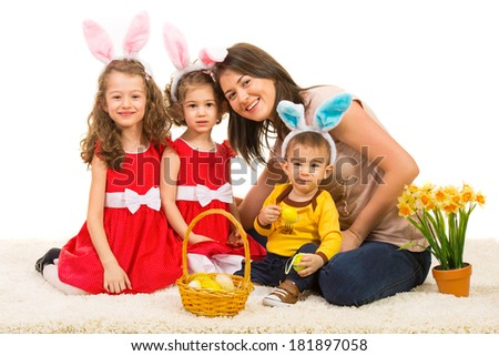 Happy mother with her kids wearing bunny ears sitting together on fur carpet - stock photo