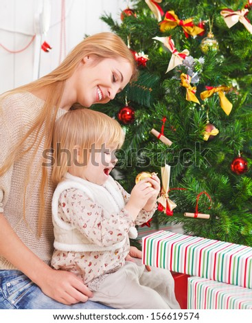Happy mother with her little daughter under the Christmas tree - stock photo