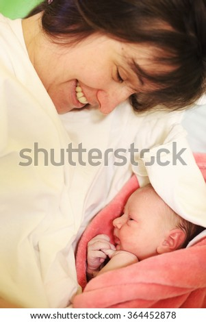 Happy mother with her newborn baby on hospital bed - stock photo
