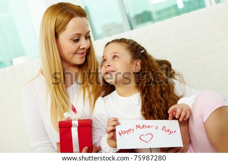 Happy mother with her pretty daughter looking at one another - stock photo