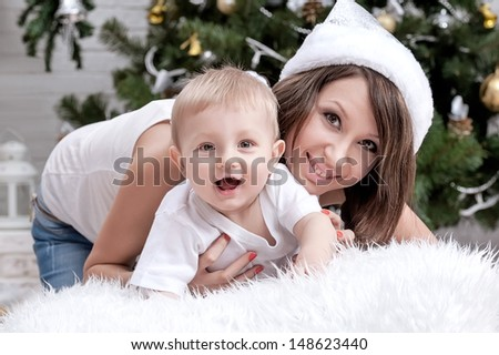 Happy mother with her son by the fireplace under the Christmas tree - stock photo
