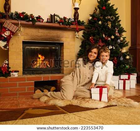Happy mother with her son in Christmas decorated house interior