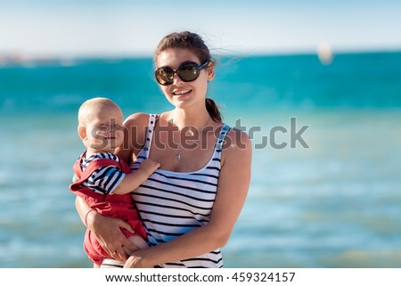 Happy mother with her son on the beach in summer day