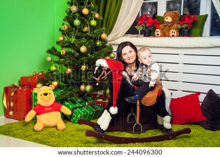 Happy mother with her son  on the toy horse under the Christmas tree - stock photo