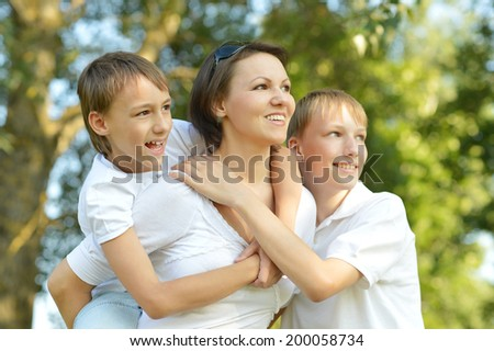Happy mother with her sons walk in the park in summer