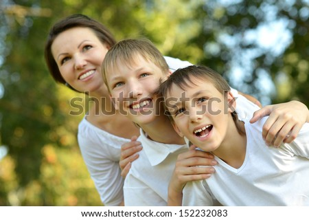 Happy mother with her two sons having fun outdoors in summer