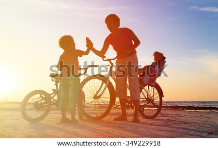 happy mother with kids biking at sunset beach