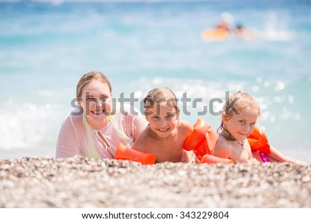 Happy mother with kids on the beach having fun
