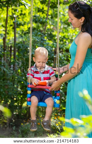 Happy mother with laughing baby sits on the swing