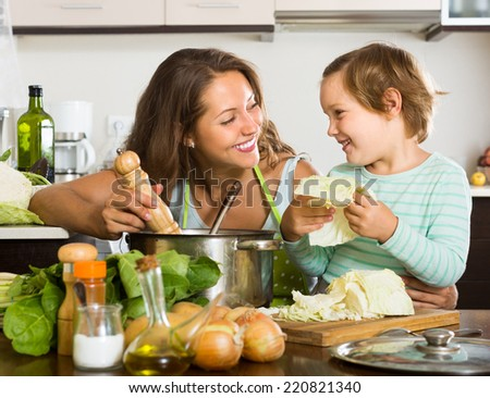 Happy mother with little daughter cooking soup together at home kitchen  - stock photo