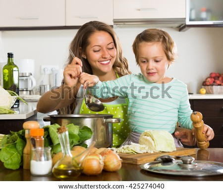 Happy mother with little daughter cooking soup together at home kitchen