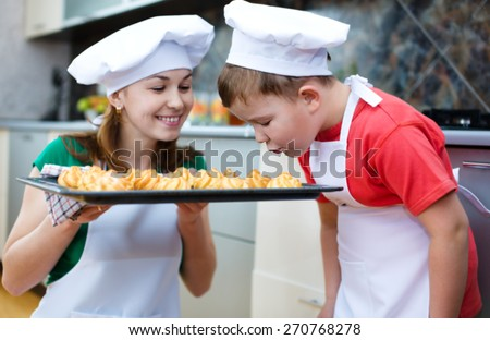 Happy mother with son making bread in the kitchen - stock photo