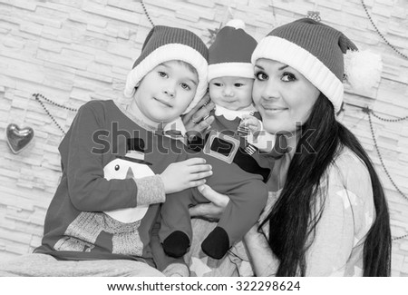 Happy mother with sons in Santa hats  ( black and white ) - stock photo
