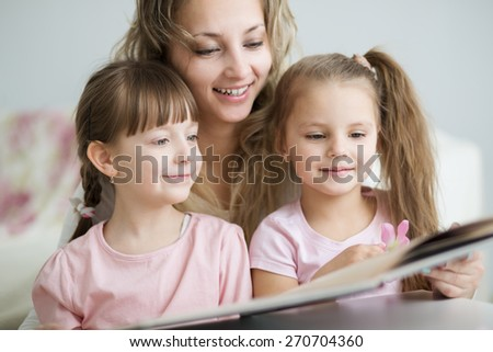 happy mother with sweet little daughters reading book - stock photo