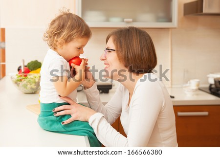 happy mother with the baby in the kitchen - stock photo