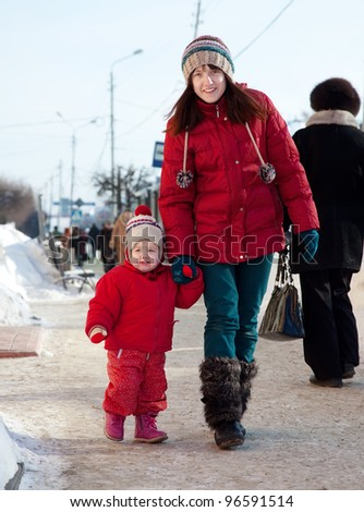 Happy mother with toddler  in winter street - stock photo