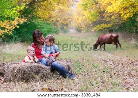 happy mother with two children in autumn park - stock photo