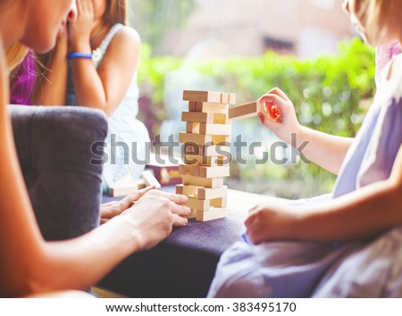 Happy mother with two children playing the wooden blocks tower at home - stock photo