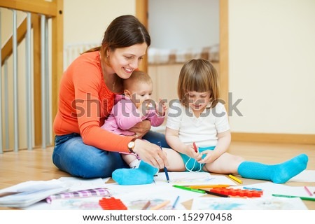 Happy mother with two children plays at home interior