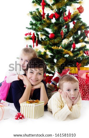 Happy mother with two children under Christmas tree with presents