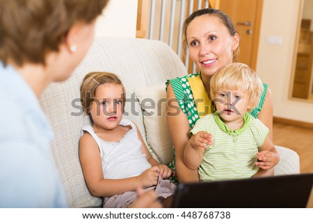 Happy mother with two daughters glad hearing words of social worker at home - stock photo