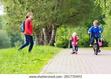 happy mother with two kids on scooter and bike in the park, family sport