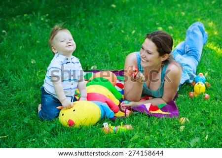 happy mother woman and baby boy kid child on background of grass in park - stock photo