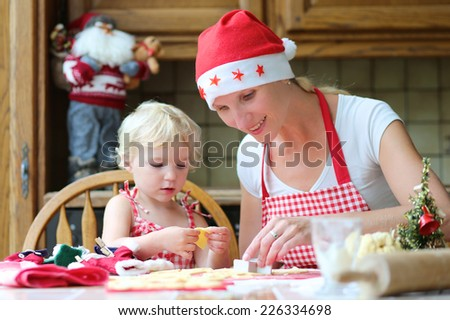 Happy mother, young woman in red apron and santa hat baking christmas cookies together with her little daughter, cute blonde toddler girl, sitting at the table in classic traditional wooden kitchen