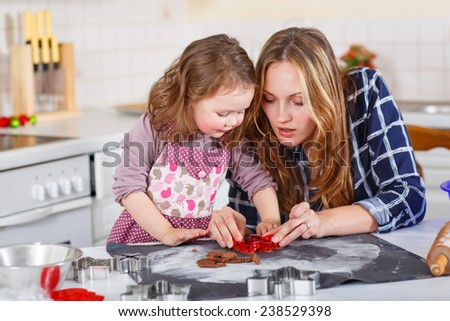 Happy mother, young woman in red santa hat baking christmas cookies together with her little daughter, cute blonde kid girl, sitting at the table in domesti? kitchen - stock photo