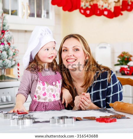 Happy mother, young woman in red santa hat baking christmas cookies together with her little daughter, cute blonde kid girl, sitting at the table in domestic kitchen - stock photo