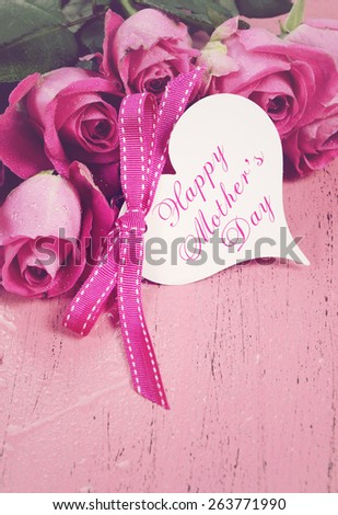 Happy Mothers Day gift of fresh pink roses on a pink distressed wood background with sample text, and applied retro vintage style filters. - stock photo