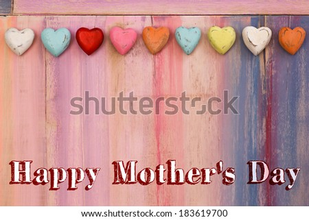 Happy mothers day message colorful painted board with wooden hearts - stock photo