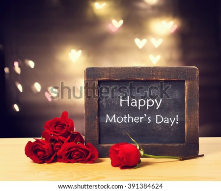 Happy Mothers day message on a small chalkboard with red roses  - stock photo