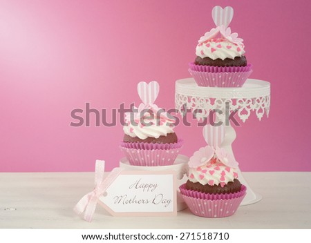 Happy Mothers Day pink and white cupcakes on retro style cake stands on vintage white wood table, with applied retro vintage style filters and added lens flare light stream. - stock photo