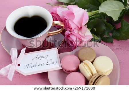 Happy Mothers Day Pink Roses and Heart Shape Tea Cup, with macarons on vintage style distressed pink wood table. - stock photo