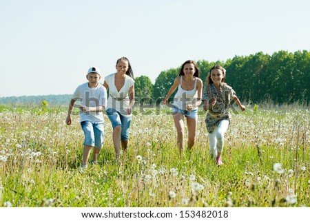 Happy mothers with teenagers running in meadow  - stock photo