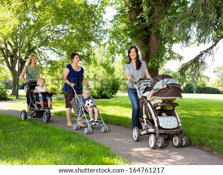 Happy mothers with their baby strollers walking together in park