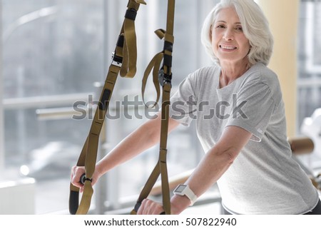 Happy motivated smiling woman using special equipment in a gym.