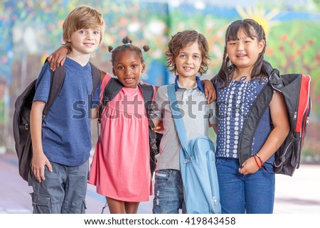 Happy multi ethnic classmates embracing in schoolyard, happiness and integration concept.