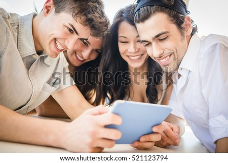 Happy multi ethnic group of friends with casual clothes enjoying life using a digital tablet and taking selfie during they're holiday in the city