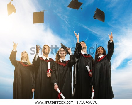 Happy multi ethnic group of graduated young students throwing hats in the air - stock photo