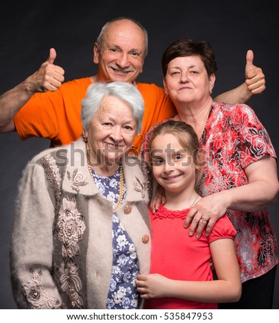 Happy multi-generation family posing in studio on a gray background
