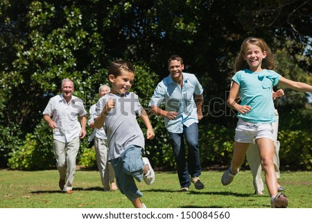 Happy multi generation family racing towards camera in a park