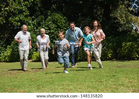 Happy multi generation family running towards camera in the park on sunny day - stock photo