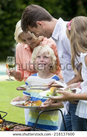 Happy multi-generation family standing at barbecue grille - stock photo