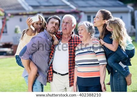 Happy multi-generation family taking a selfie in garden - stock photo