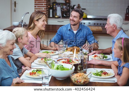 Happy multi generation family with grandparents sitting at dining table - stock photo