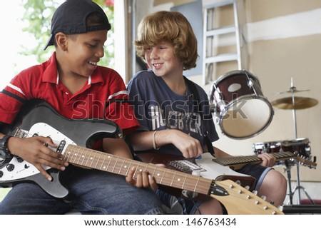 Happy multiethnic boys playing guitars in garage - stock photo