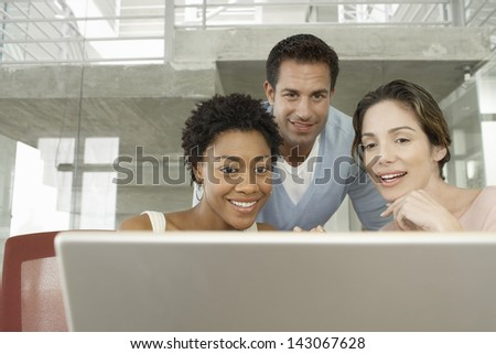 Happy multiethnic business people using laptop in conference room - stock photo