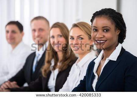 Happy Multiethnic Businesspeople Sitting In Office With Graph On Desk